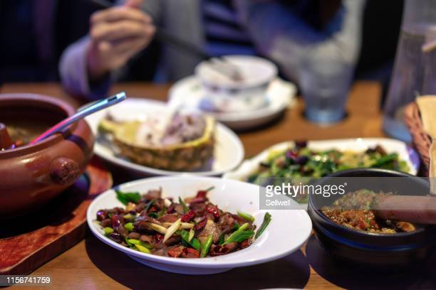 asian woman tasting yunnan traditional food - kunming stock pictures, royalty-free photos & images