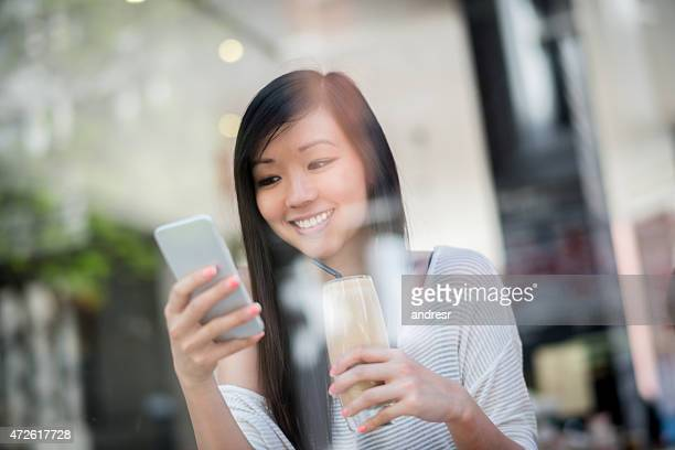 Asian woman texting while drinking a frappuccino