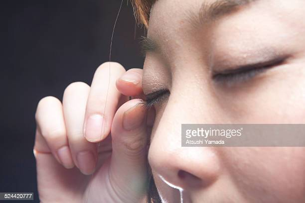 asian woman touching her eyelid - eyelid stock photos and pictures