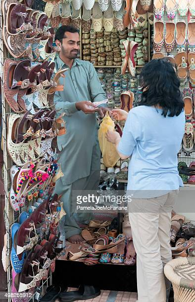 Asian Woman Tourist Paying For Shoes with Cash, Dubai, UAE