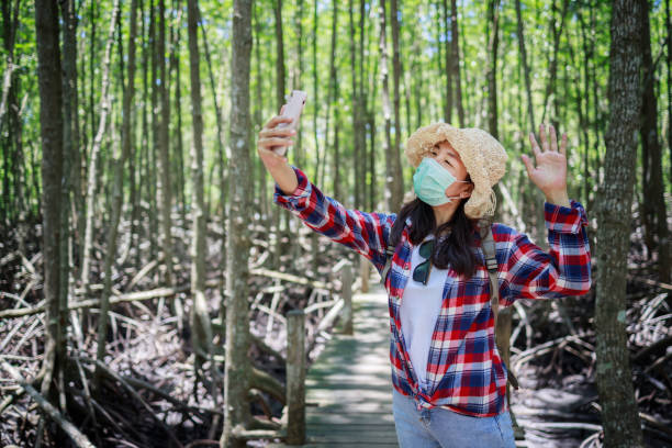 Asian woman traveler selfing by smartphone and wearing masks cover the face for protection from germ spread while traveling in the mangrove forest