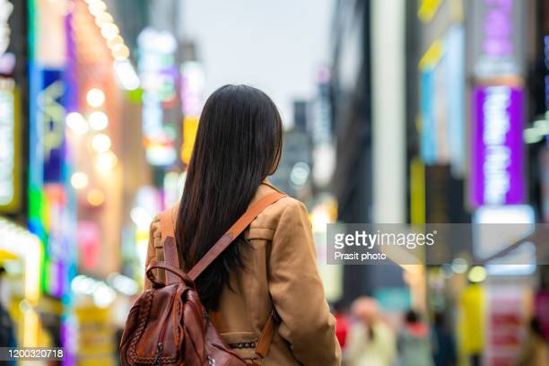 asian woman traveler walking at night with the light from fluorescent bulbs in myeongdong shopping street at seoul, south korea. - corée du sud photos et images de collection
