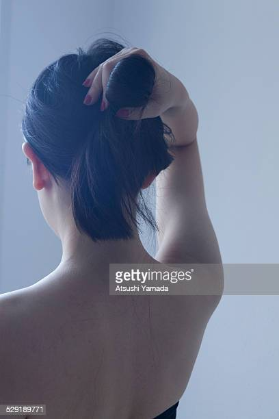 Asian woman tying up hair,rear view