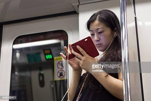 Femme asiatique de taper sur Smartphone dans le métro, Singapour