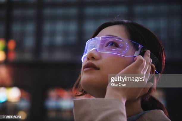 asian woman using a smart glasses in front of an office building - wearable computer stock pictures, royalty-free photos & images