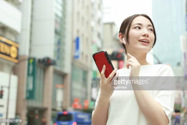 スマートフォンを使用してアジアの女性 - 仕事後 ストックフォトと画像