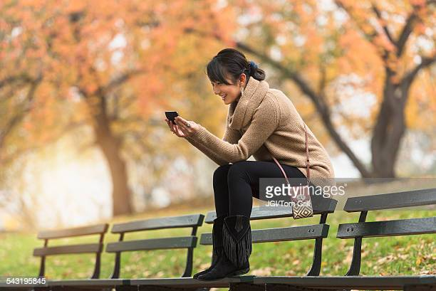 asian woman using cell phone on park bench - multi coloured purse stock photos and pictures