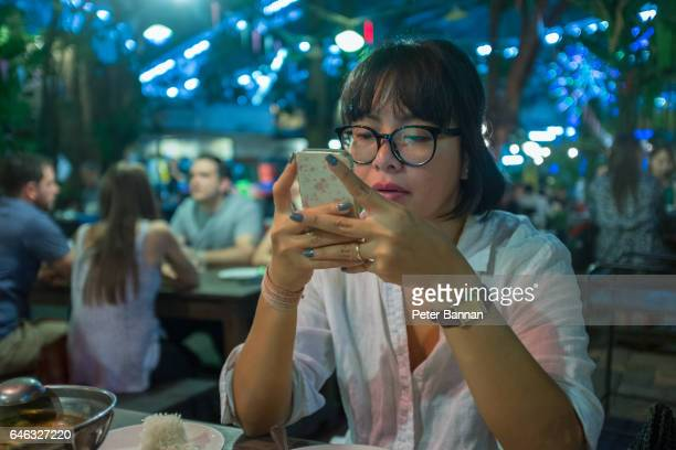 Asian woman using handphone in street restaurant, night, Bangkok Thai restaurant