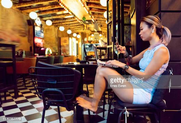 Asian woman using laptop and mobile phone in pub