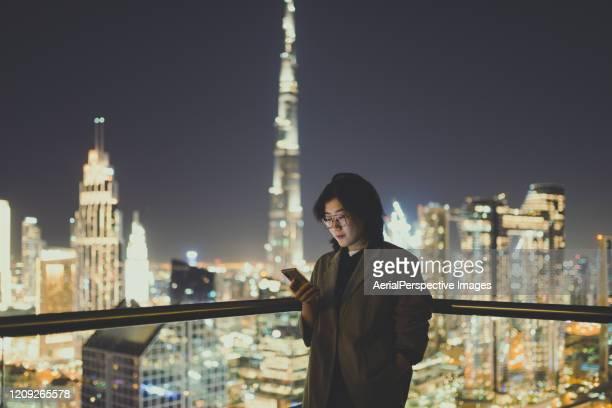 asian woman using mobile phone on rooftop / dubai, uae - midden oosterse etniciteit stockfoto's en -beelden