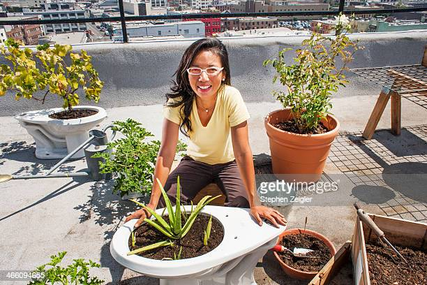 Asian woman using old toilets as planters