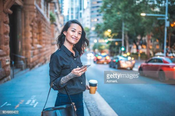 Asian woman using phone and waiting for taxi in Sydney