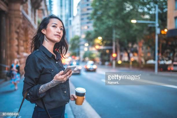 femme asiatique en utilisant le téléphone et en attente de taxi à sydney - attendre photos et images de collection