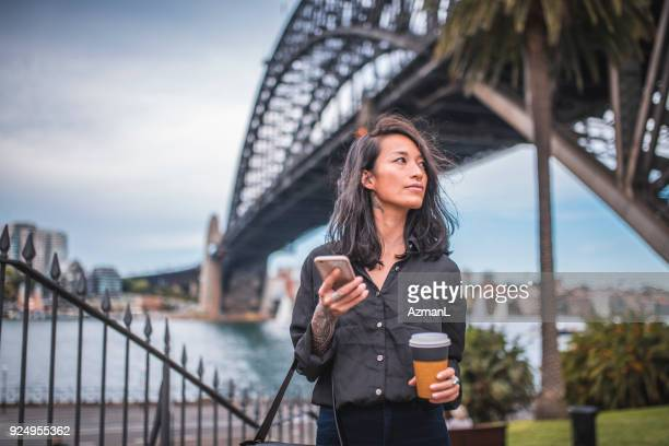 asian woman using phone in sydney - australia stock pictures, royalty-free photos & images