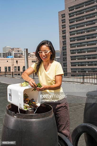 Asian woman using rooftop compost bin