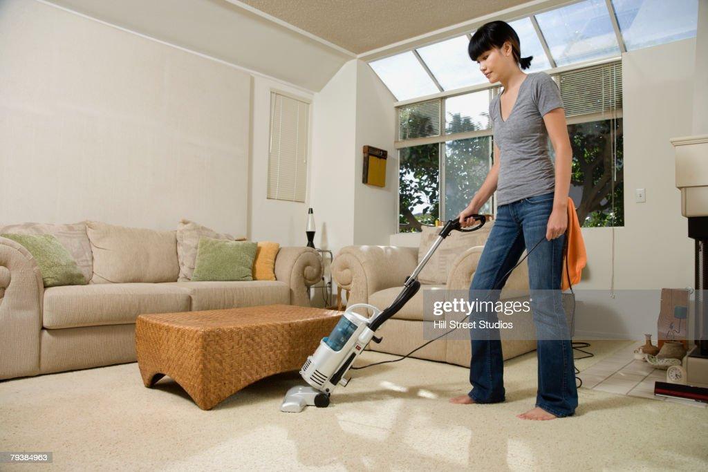 Asian woman vacuuming : Stock Photo