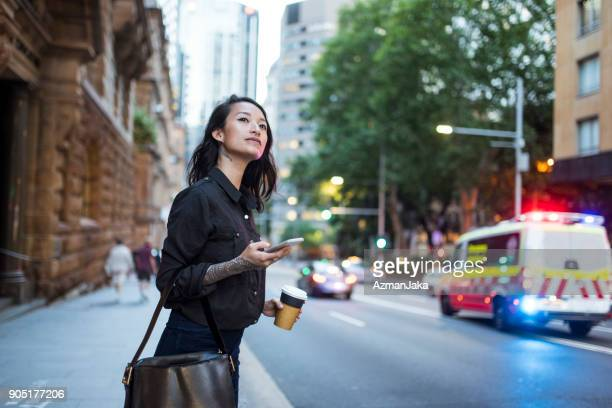asian woman waiting for an uber and drinking coffee - new south wales stock pictures, royalty-free photos & images