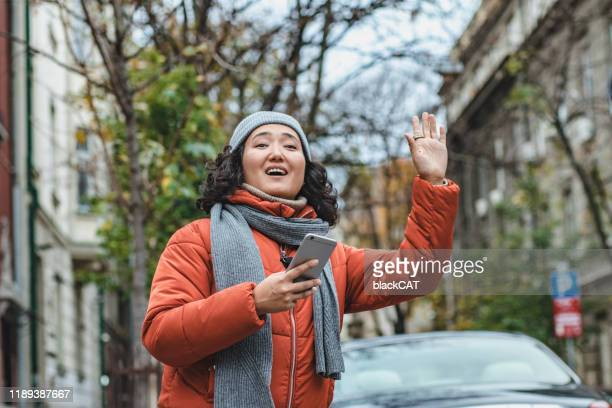 asian woman waiting for taxi - taxiing stock pictures, royalty-free photos & images
