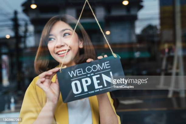 asian woman waitress holding open sign in cafe bar flipping hanging on door window. small business owner and startup with cafe shop. installing open and close label concept - opening event stock pictures, royalty-free photos & images
