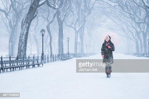 Asian woman walking in snowy park