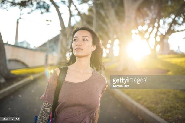 asian woman walking in the park in sydney - mid adult women stock pictures, royalty-free photos & images