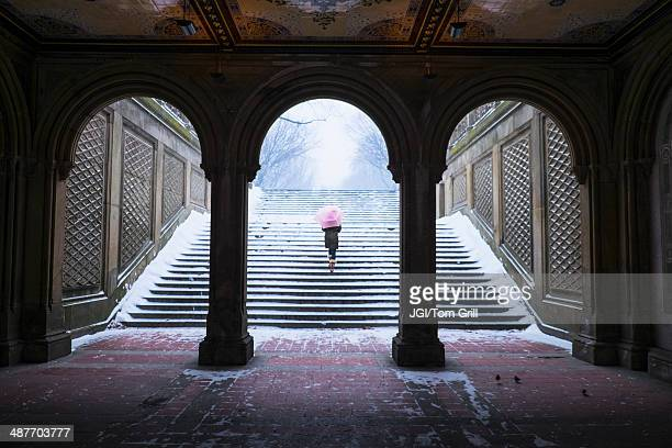 Asian woman walking up steps into snow