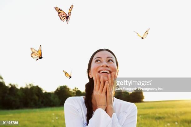 Asian woman watching butterflies in meadow