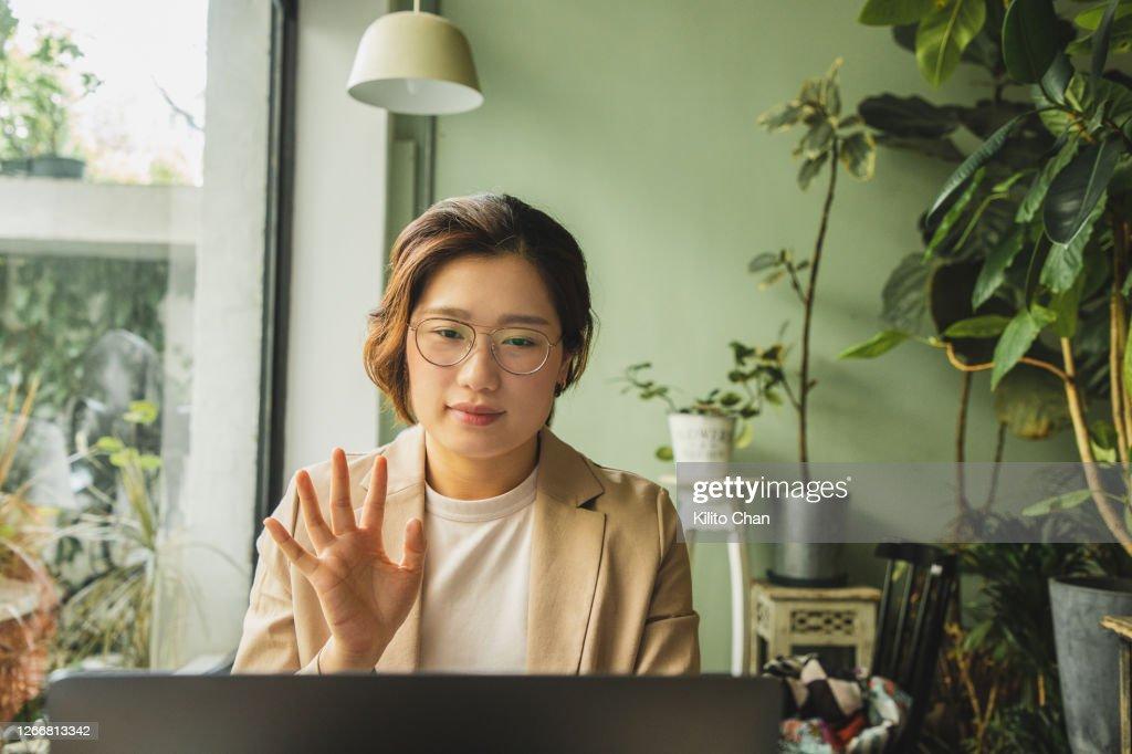 Asian woman waving at a laptop at a cafe : Stock Photo
