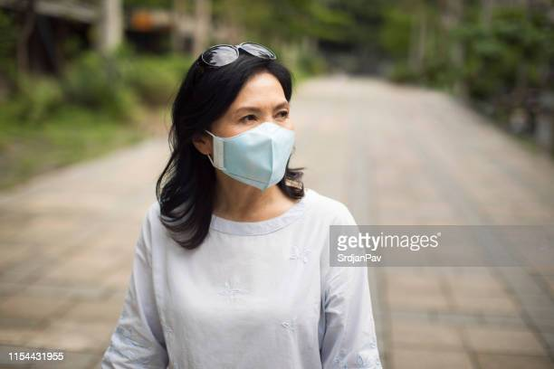 asian woman wearing a face mask while walking the streets of taipei - surgical mask stock pictures, royalty-free photos & images