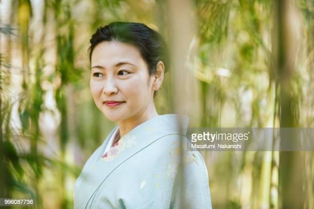 Asiatische Frau trägt einen Kimono zu Fuß im Bambushain