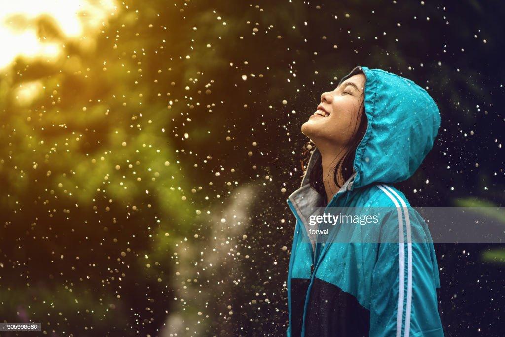 アジアの女性のアウトドア レインコートを着るします。彼女は幸せです。 : ストックフォト