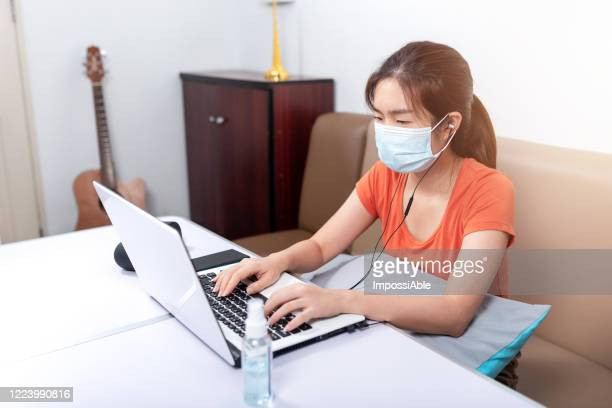 asian woman wearing a surgical mask to protect the corona virus or covid 19 while working at home in front of laptop - impossiable stock pictures, royalty-free photos & images