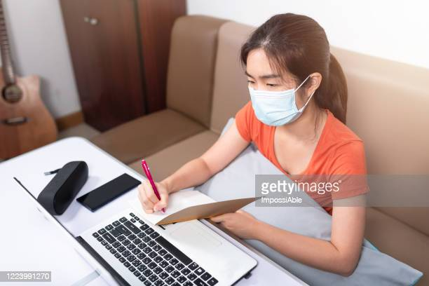 asian woman wearing a surgical mask to protect the corona virus or covid 19 while working at home in front of the laptop taking notes - impossiable stock pictures, royalty-free photos & images