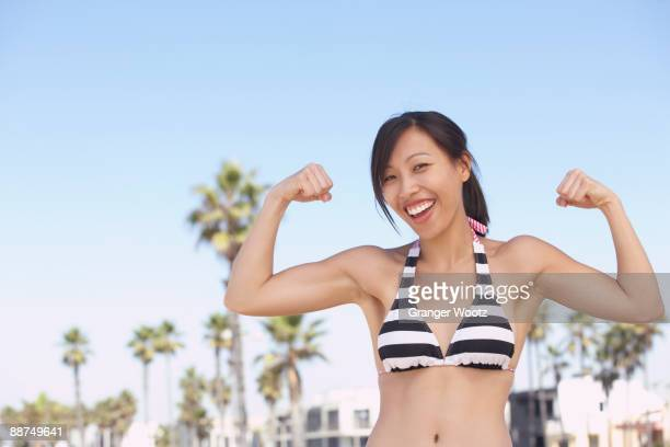 asian woman wearing bikini showing muscles - female exhibitionist stock photos and pictures