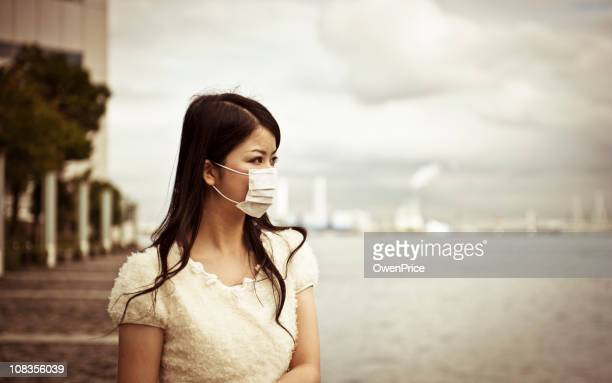 Asian woman wearing face mask with a blurred background