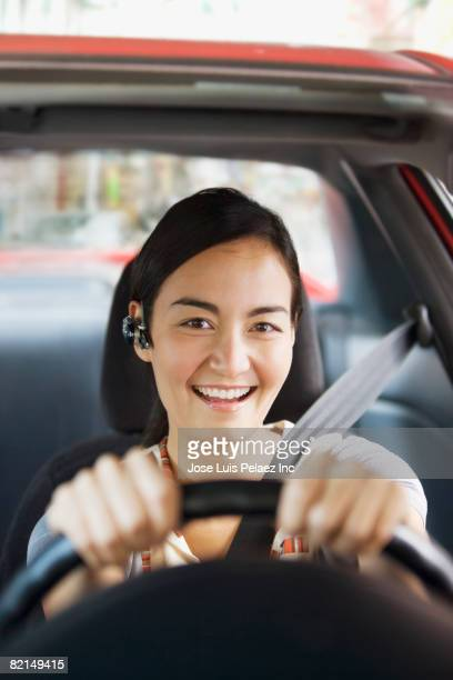 Asian woman wearing hands free device in car