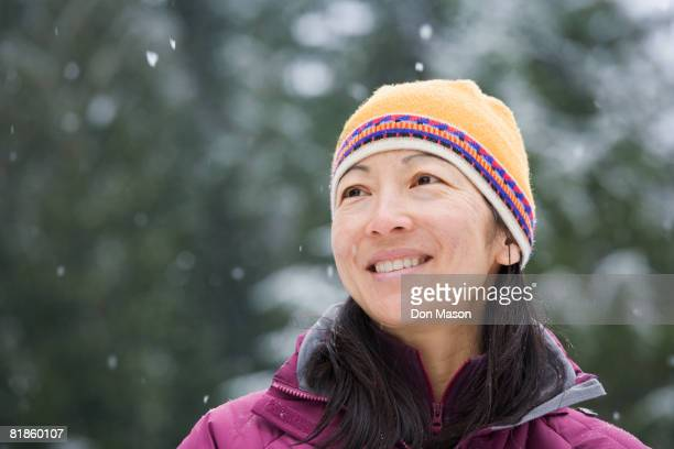 Asian woman wearing hat in snow