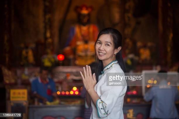 asiatisk kvinna bär traiditional qipao be i buddist tempel - prayer pose greeting bildbanksfoton och bilder