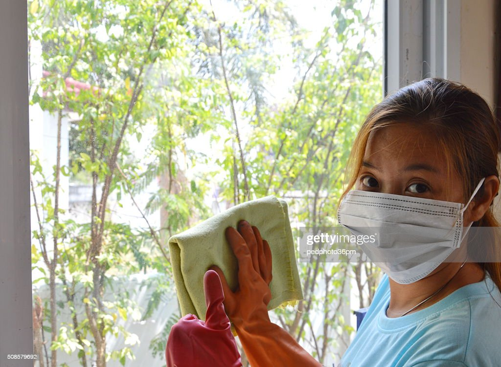 Asian woman wipe the glass diligently but still be fine : Stock Photo