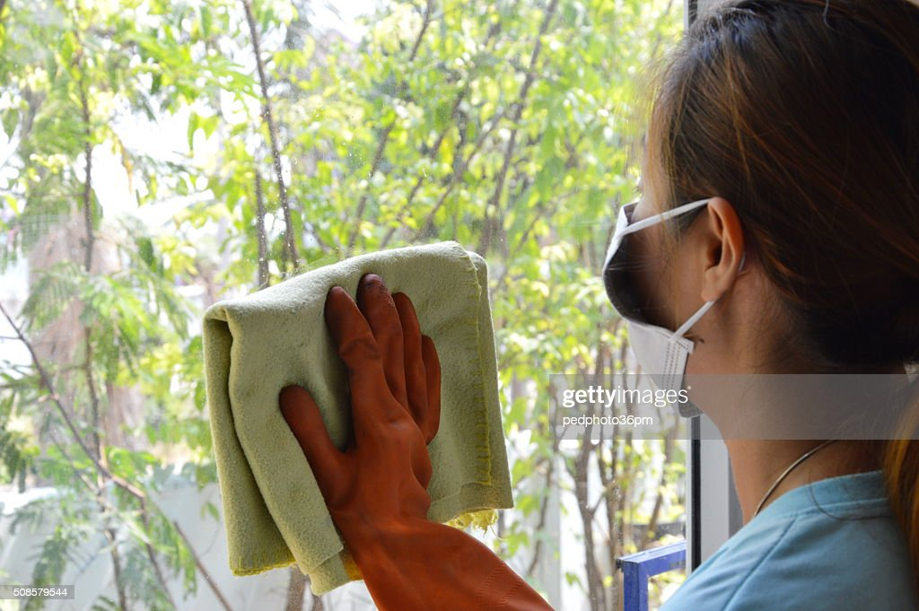 Asian woman wipe the glass in home : Stockfoto