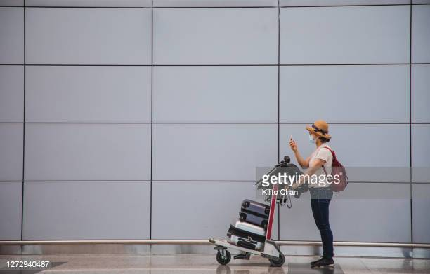asian woman with a luggage cart using phone at the airport terminal - passagier stock-fotos und bilder