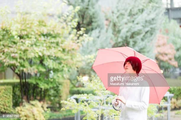 事務所ビルの庭に赤い傘とアジアの女性が歩いています。