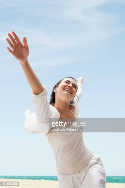 Asian woman with arms outstretched on beach