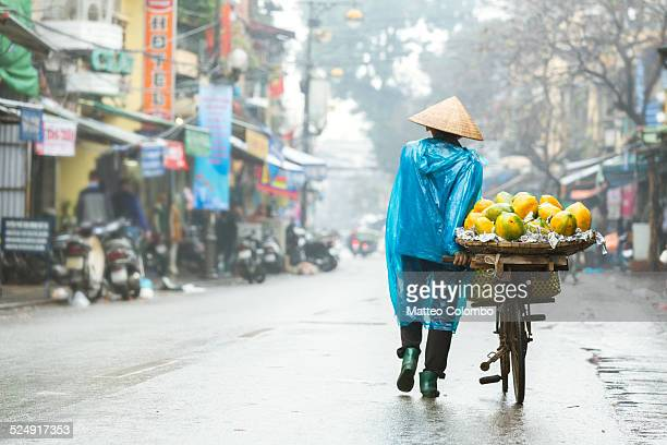 Asian woman with bicycle in the streets of Hanoi