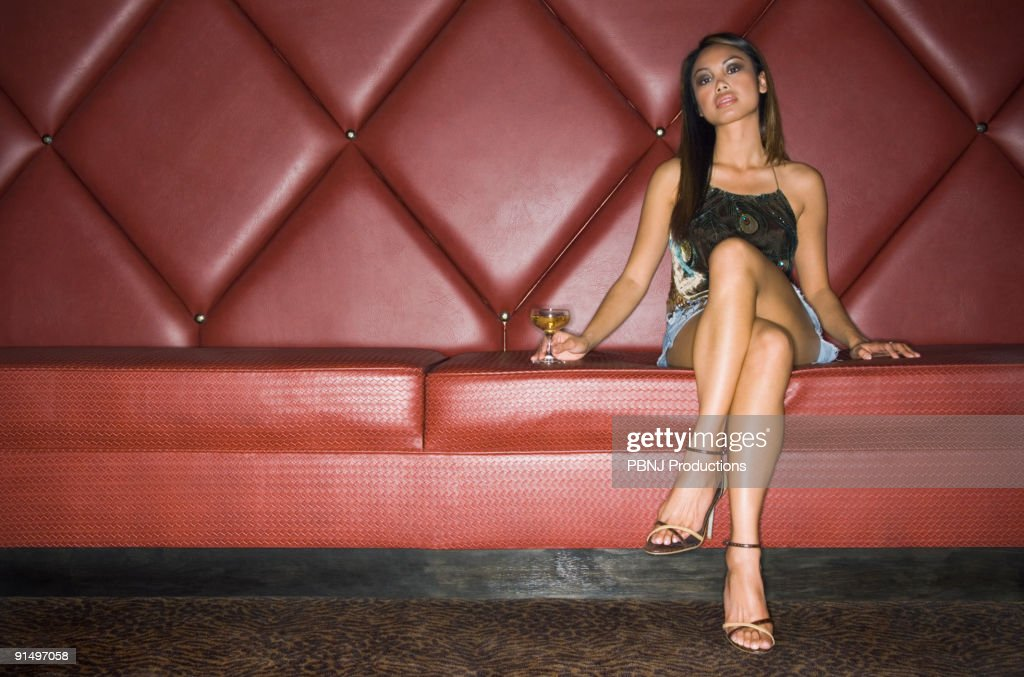Asian woman with cocktail in cushioned booth : Stock Photo