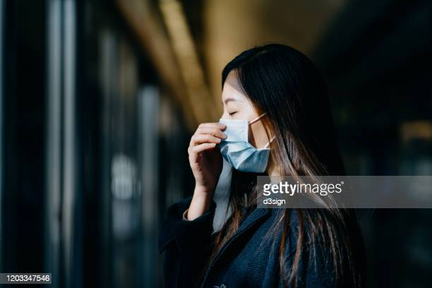 asian woman with eyes closed wearing protective face mask commuting in the city and waiting for subway in platform - epidemia foto e immagini stock