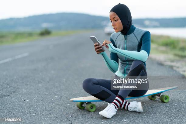 asian woman with hijab and skateboard standing on road and using smart phone - uae heritage stock photos and pictures