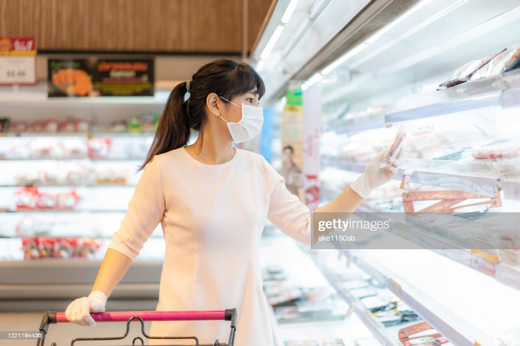 Asian woman with hygienic mask and rubber glove with shopping cart in grocery and looking for fresh meat pack to buy during covid-19 outbreak for preparation for a pandemic quarantine : Stock Photo