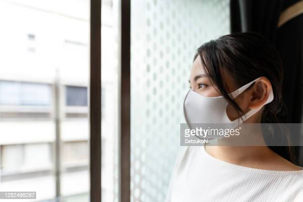 asian woman with mask standing by the window - state of emergency stock pictures, royalty-free photos & images