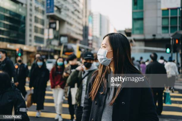asian woman with protective face mask crossing road in busy downtown city street against crowd of pedestrians and highrise urban buildings - epidemi bildbanksfoton och bilder